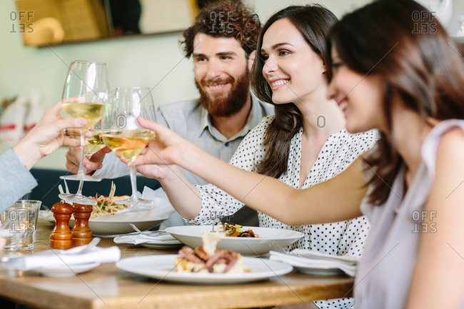 friends toasting and celebrating at lunch in fancy restaurant