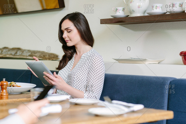 Young business woman using her tablet at lunchtime in restaurant