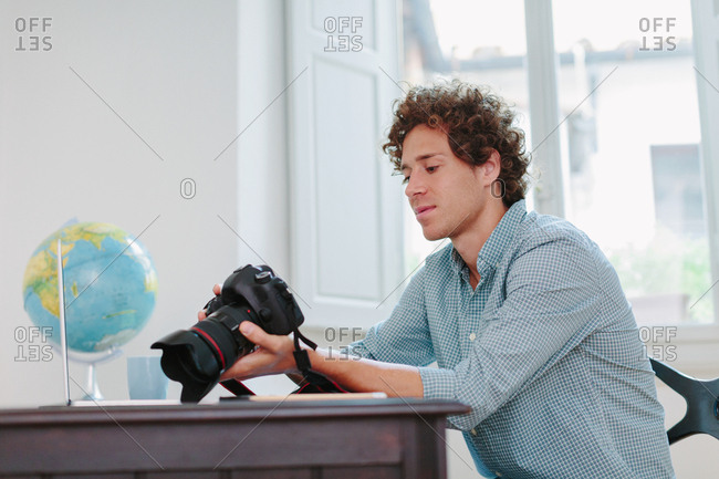 Young man reviewing photos on an slr camera