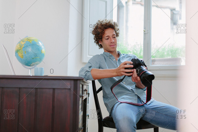 Young man leaning on desk looking at a camera