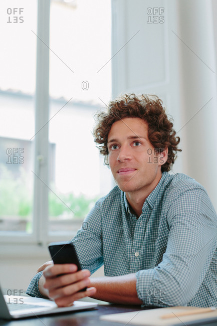 Happy young man holding a phone