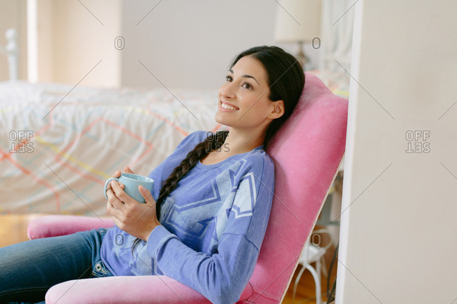 Young woman holding a mug in an armchair
