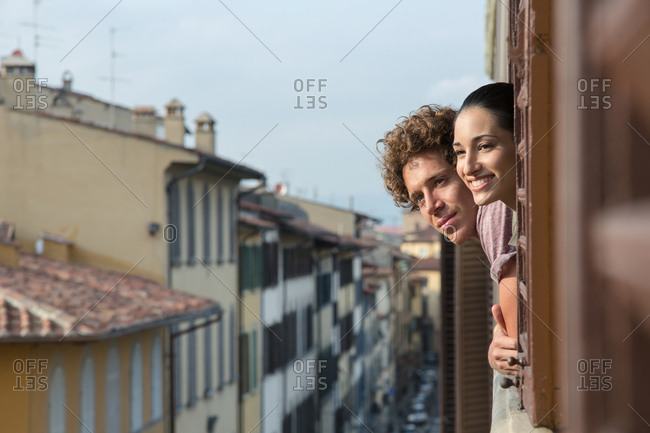 Happy young couple looking out of a window