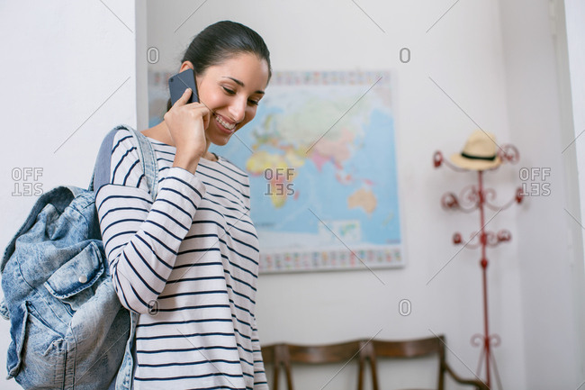 Young woman talking on the phone about to leave the house