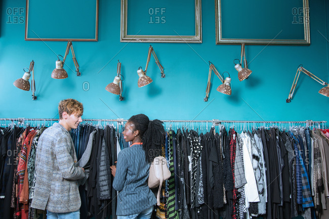 Young couple standing in front of a rack of clothes