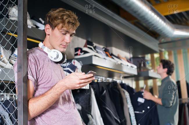 Young man using his mobile phone in a shop