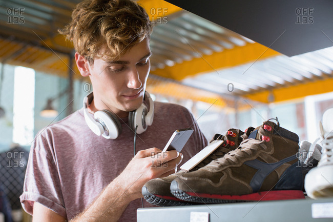 Young man checking price of shoes