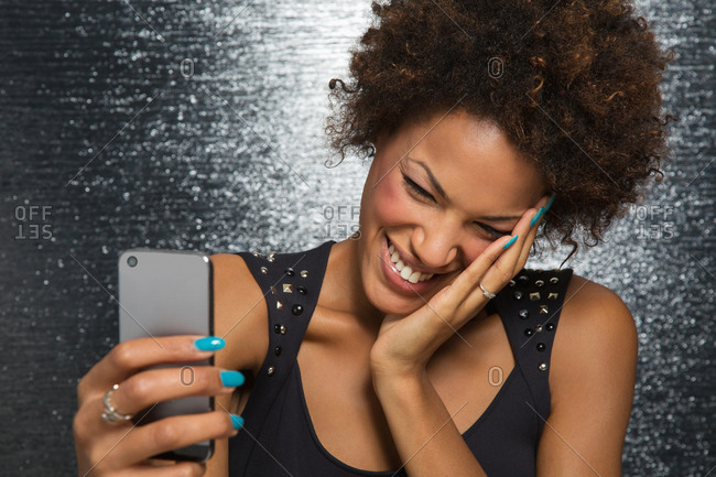 Portrait of beautiful young afro American woman at party with mobile phone