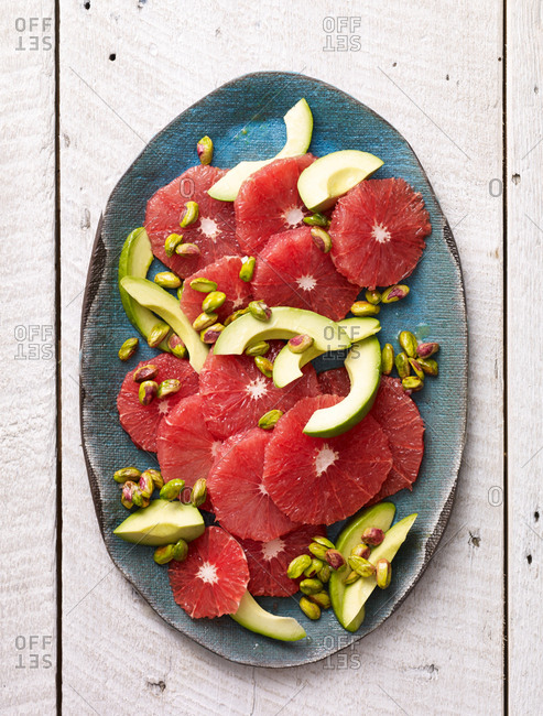 Fruit salad with grapefruit, avocado and pistachios on a platter