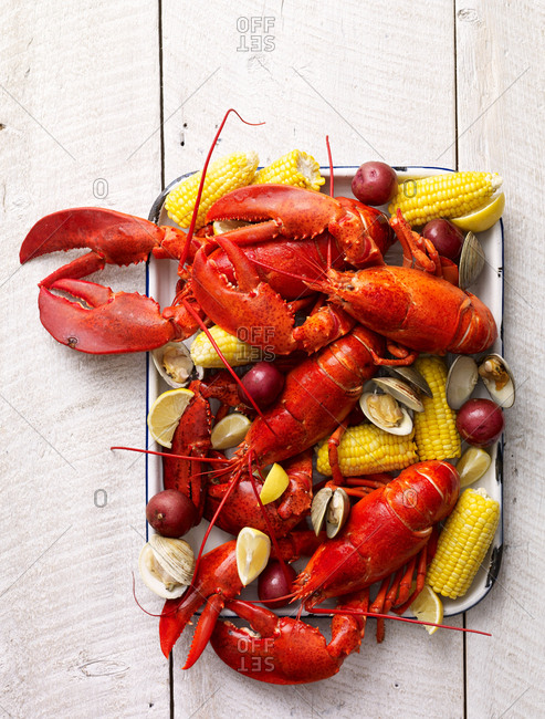 Seafood boil with lobster, corn and potatoes on a tray