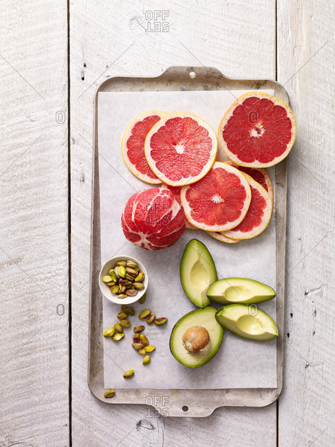 Ingredients for a grapefruit salad with avocado and pistachios