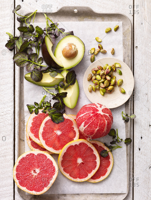 Ingredients for a grapefruit salad with avocado, pistachios and herbs