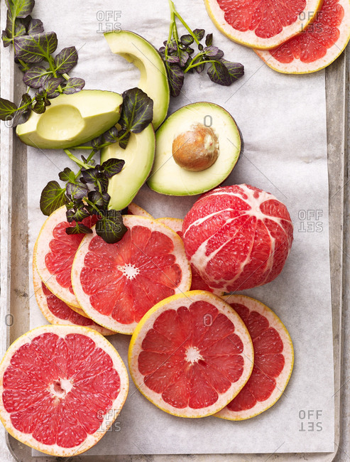 Ingredients for a grapefruit salad with sliced avocado and herbs