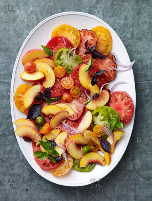 Peach and tomato salad on a white serving dish