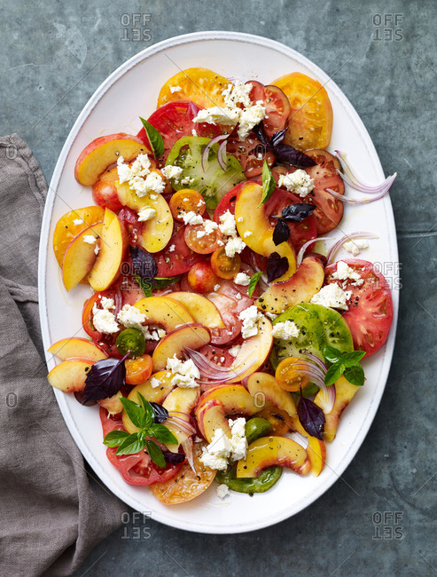 Peach and tomato salad on a white serving dish with crumbled cheese