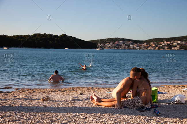Young couple kissing on a beach at sunset