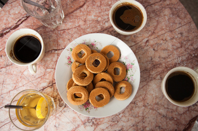 Ring cookies and coffee cups on a pink marble table