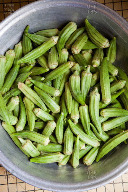 Large metal cooking pot full of whole green okra