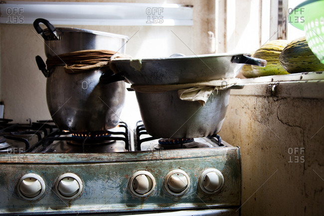 Cooking pots stacked on burners on a gas range in a Senegalese kitchen