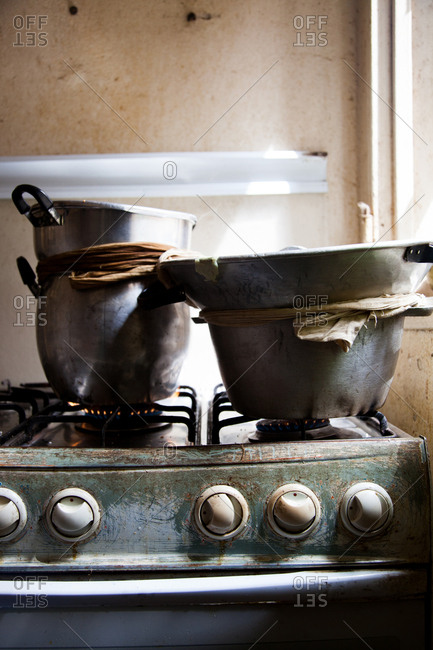 Pots of food cooking on a gas range in a Senegalese kitchen