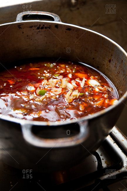 Stew with a red broth cooking on a stove top in Senegal