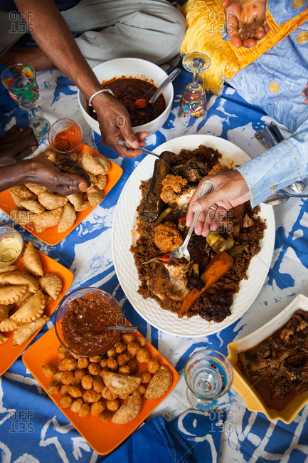 People eating spoonfuls of food from a meal served family style in Senegal