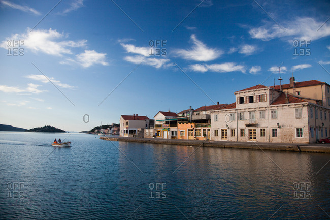 Croatia - June 27, 2012: Small boat cruising by buildings on a waterfront village
