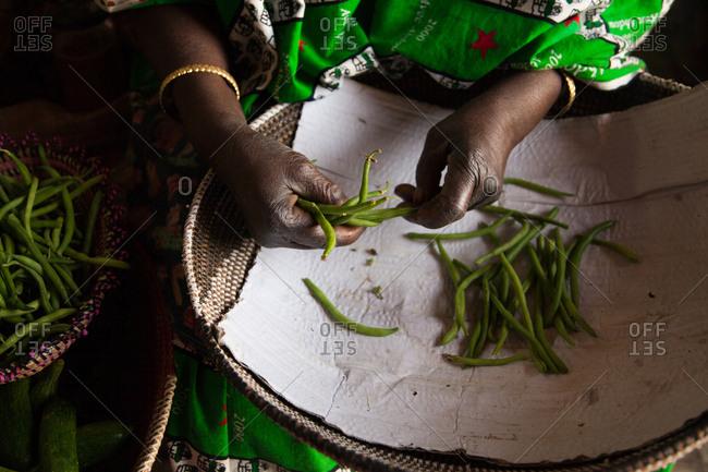 Dakar, Senegal - June 3, 2010: Woman preparing green beans in a basket in her lap