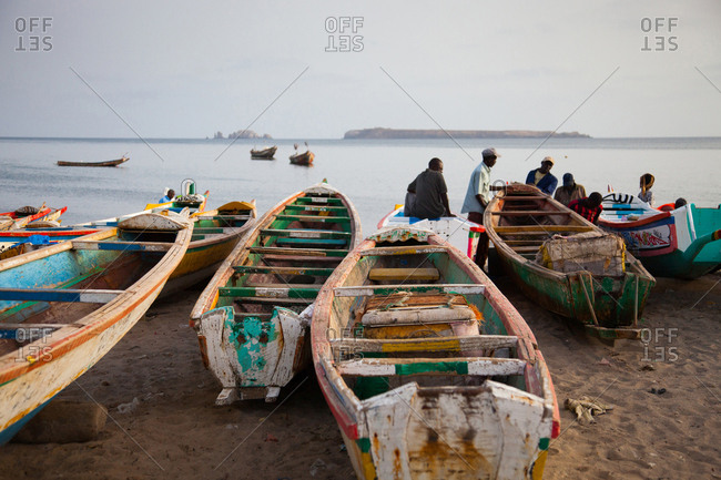 Dakar, Senegal - June 3, 2010: Men and colorful fishing boats on a beach at sunset