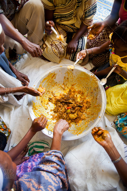 Dakar, Senegal - June 3, 2010: Family gathered with spoons around a large bowl of food