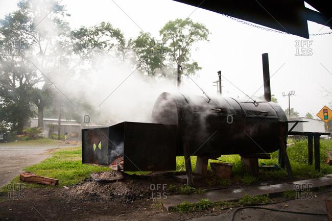 Large barrel smoker smoking near a cement patio