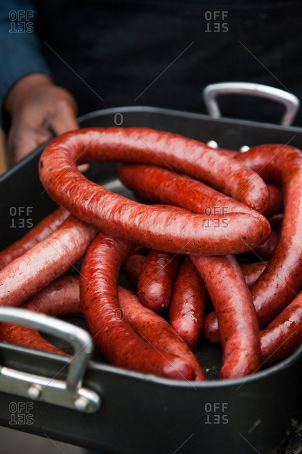 Smoked sausages in a large metal serving pan