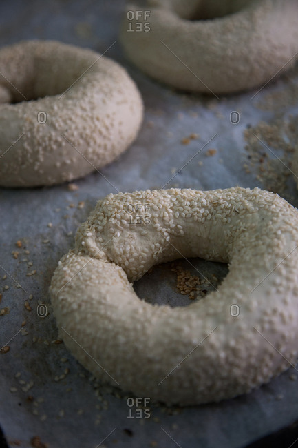 Rings of raw arkatena bread dough covered with sesame seeds
