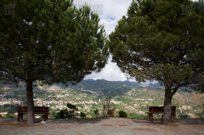 Park benches beneath trees overlooking a village in a valley