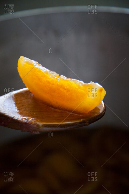 Spoonful of orange preserves over a cooking pot