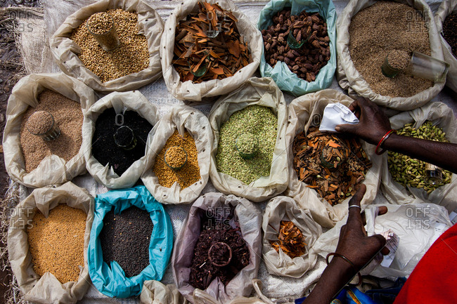 Woman scooping up spices into a container at a spice market
