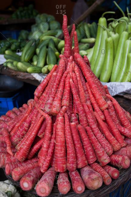 Fresh red carrots and other vegetables on display at a market