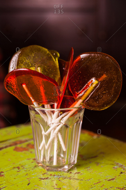 Orange and yellow lollipops in a glass on a table