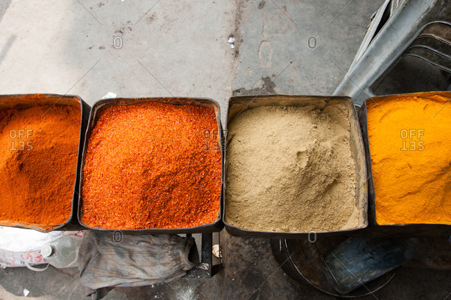 Delhi, India - March 1, 2007: Bins with a variety of colorful spices for sale in a market