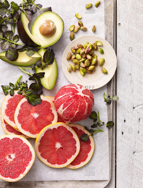 Ingredients for a grapefruit salad with pistachios, herbs and avocado