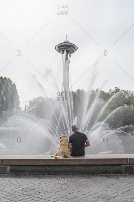 Seattle, Washington, USA - August 28, 2016: Caucasian man and dog sitting on fountain near tower