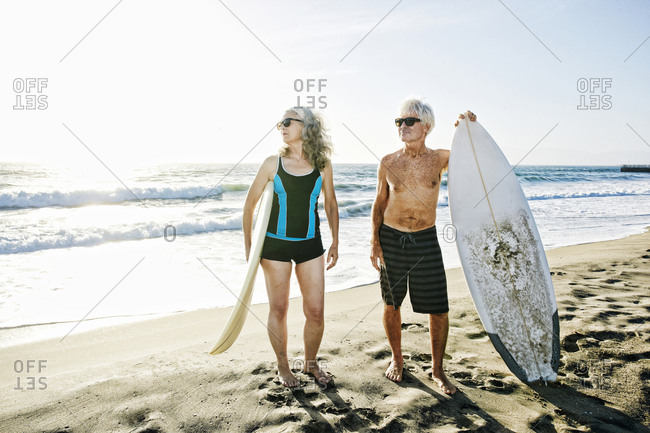 Older Caucasian couple standing on beach holding surfboards