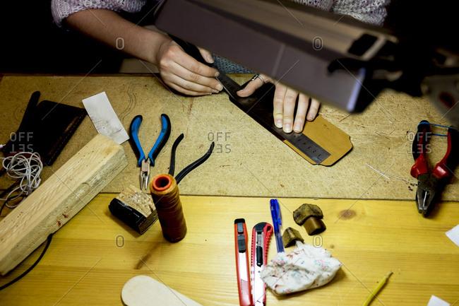 Hands of Caucasian man using ruler in workshop