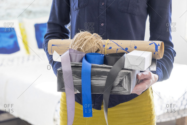 Midsection of Caucasian woman holding box and ribbons