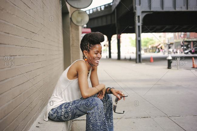 African American woman with braids sitting on ledge and laughing