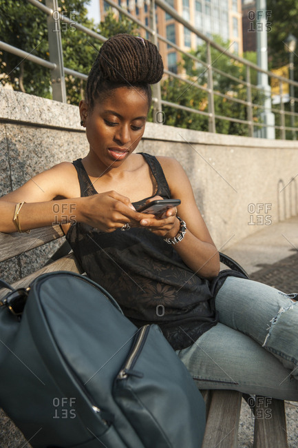 African American woman on bench at park texting on cell phone