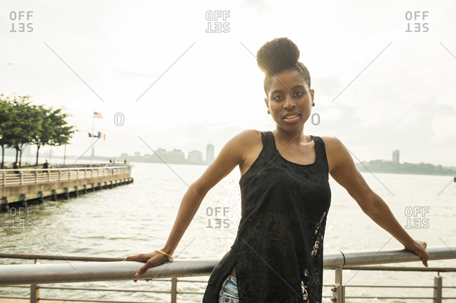 Portrait of African American woman leaning on railing at waterfront