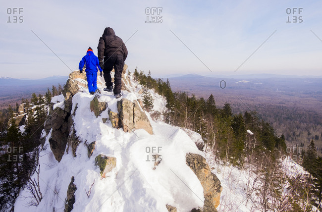 Caucasian men hiking on mountain in winter