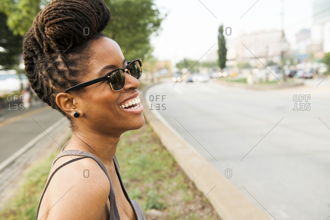 African American woman with braids laughing near street