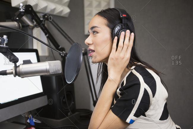 Thai transgender woman using headphones and microphone
